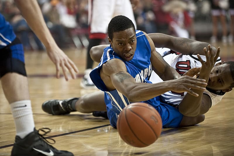 Two basketball player on the ground looking at basketball