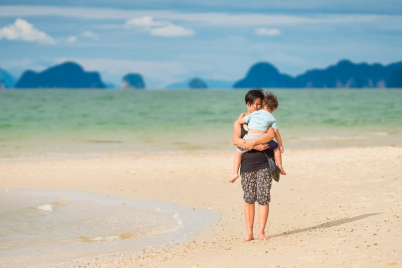 Woman carrying baby on sea shore