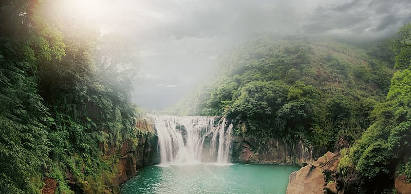 Waterfalls between green trees under white clouds during daytime