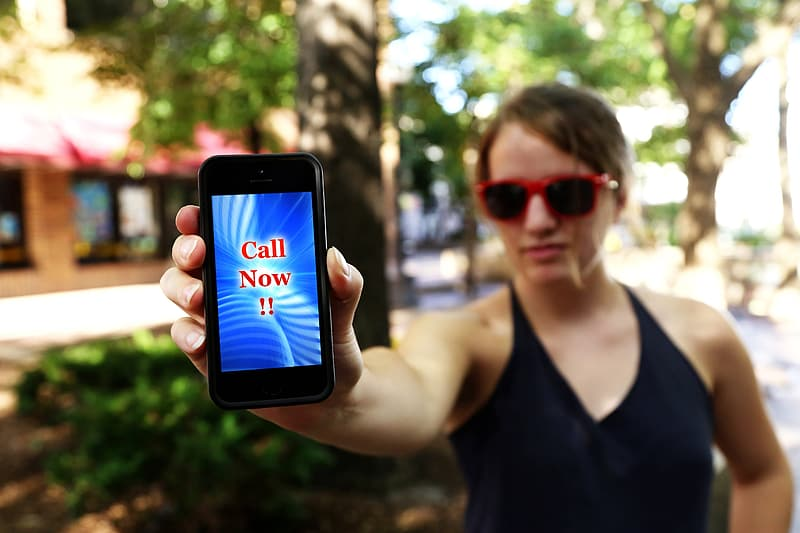 Woman wearing black v-neck shirt holding smartphone call now