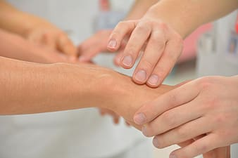 Person massaging another person's hand