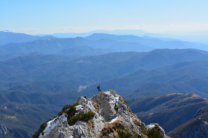 Man on top of rock mountain during daytime