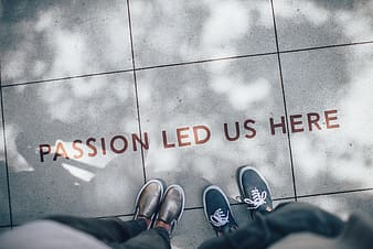 Two persons standing on passion led us here flooring