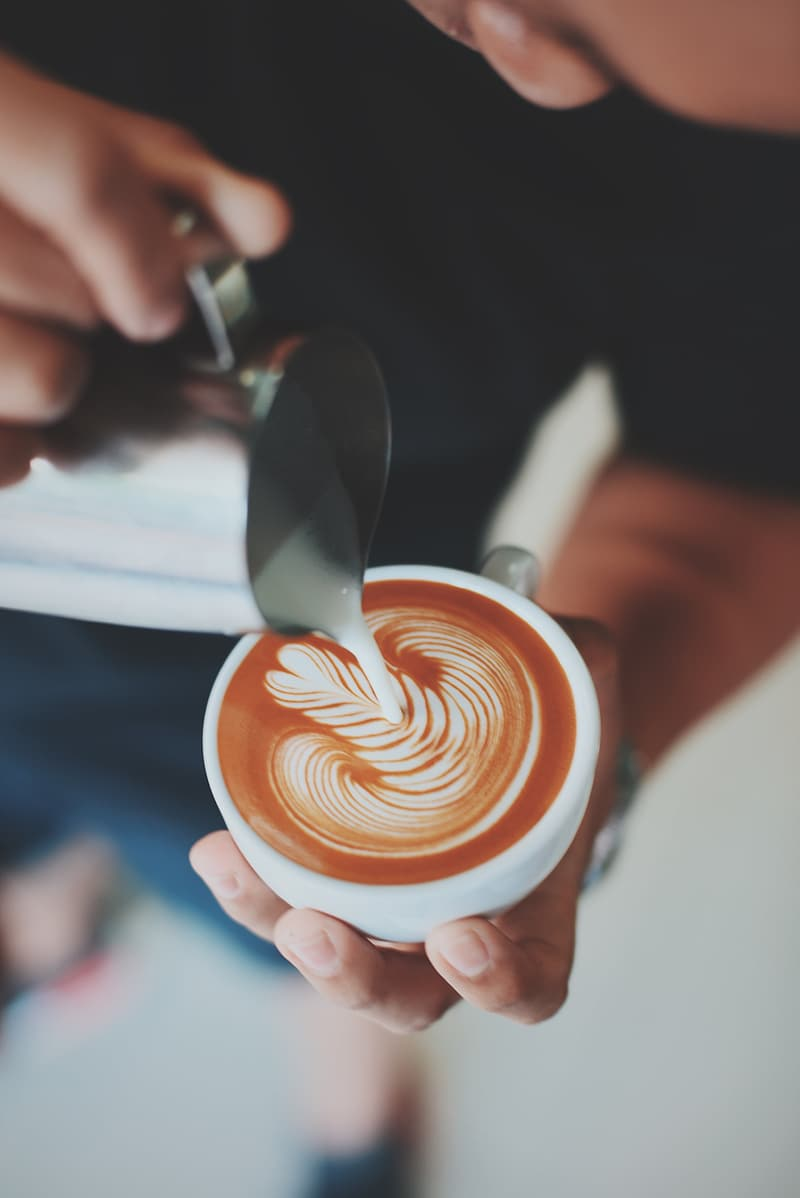 Person pouring foam topping on latte