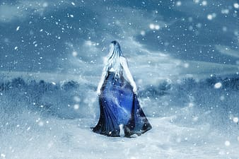 Woman in blue dress surrounded by snowy trees photo