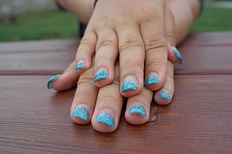 Woman placing her hands with blue manicure on table