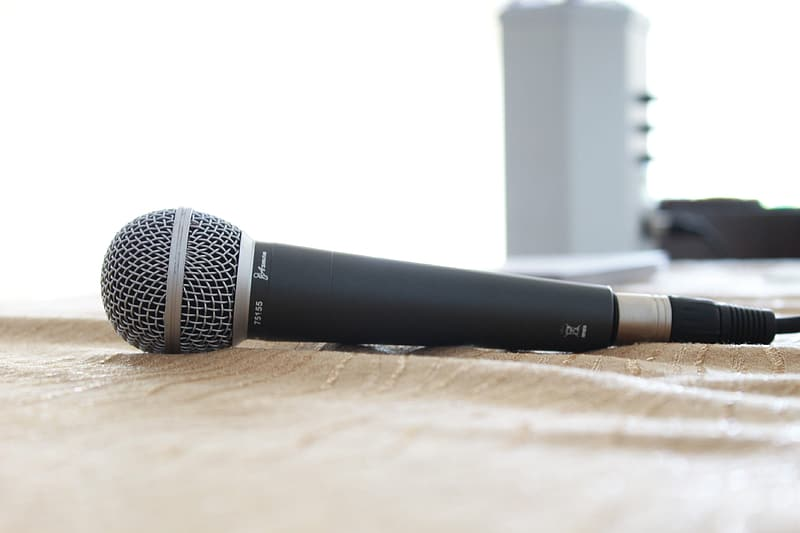 Black and gray corded microphone on brown textile