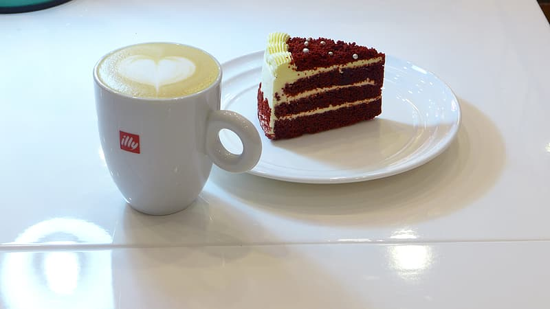 White ceramic mug with saucer and sliced of cake