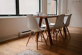 Rectangular brown wooden dining table and white plastic chairs