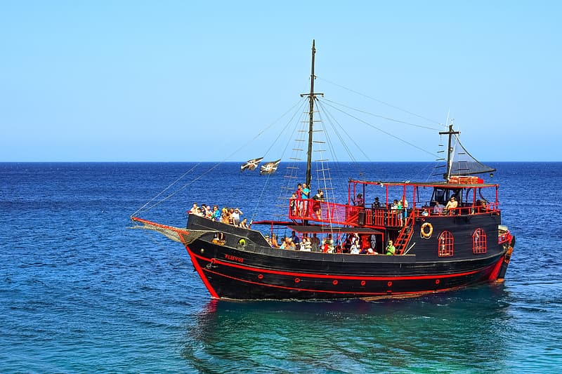 Red and black ship on sea during daytime