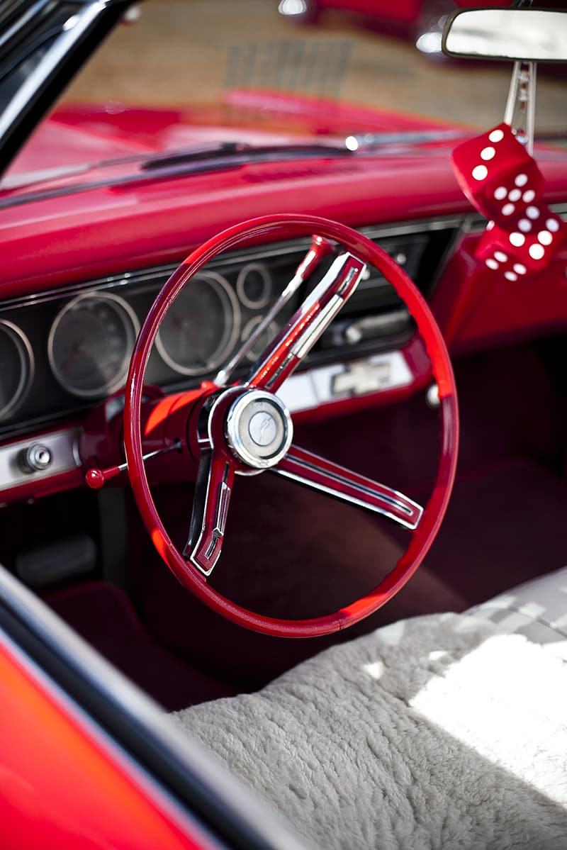 Selective focus photography of red vehicle steering wheel