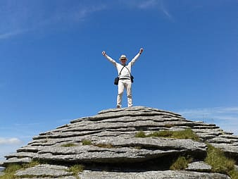 Man standing on rock mountain under blue sky