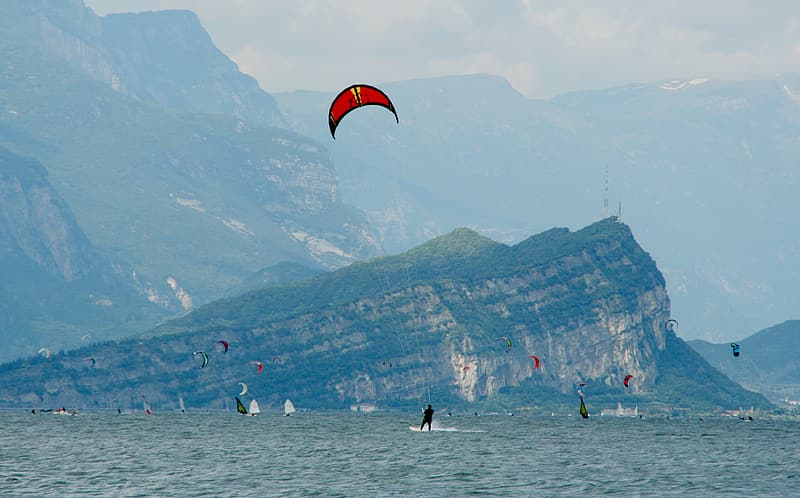 People on beach with red and yellow parachute over mountains during daytime