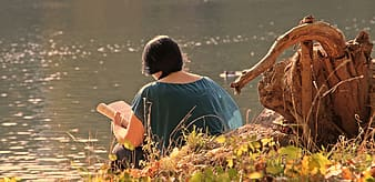Woman in blue shirt sitting on brown rock near body of water during daytime