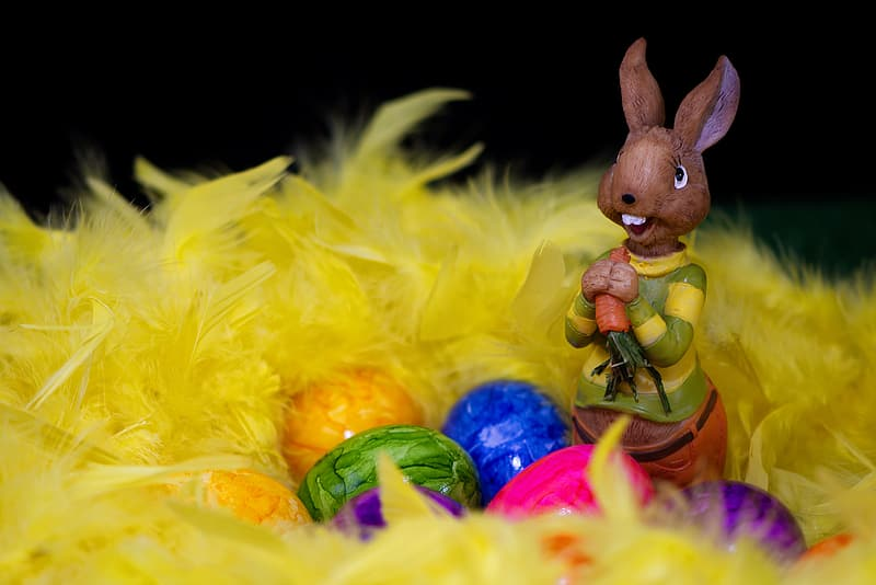 Brown rabbit figurine beside yellow and blue egg