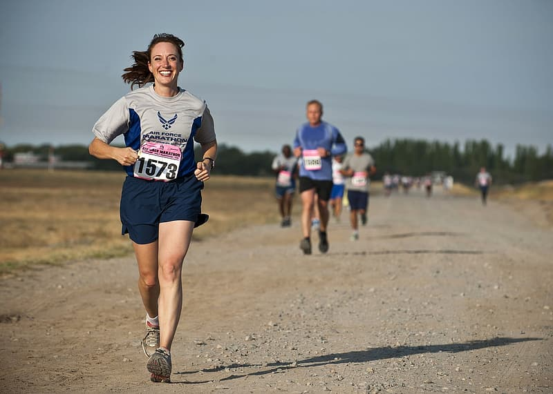 Woman in grey shirt running on marathon