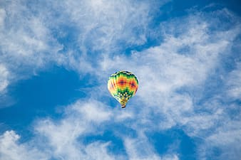 Multicolored air balloon flying on sky