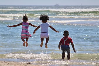 Three children playing on seashore during daytime