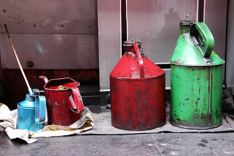 Four assorted-color gas cans near gray wall