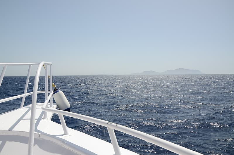White boat with island at distance