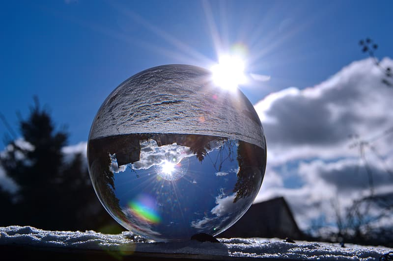 Clear glass ball on gray sand under blue sky during daytime