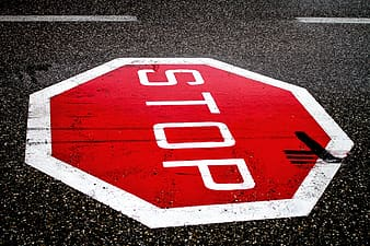 Red and white stop signage on gray asphalt surface