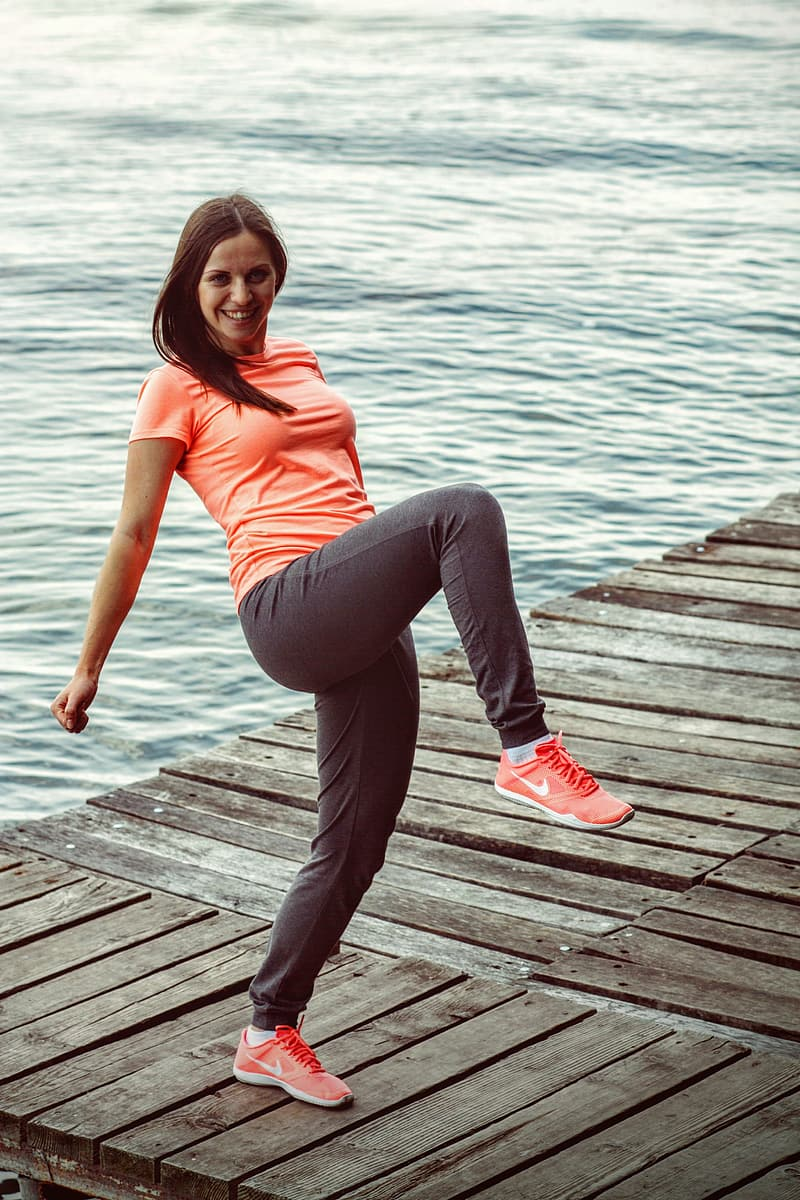 Woman wearing orange crew-neck t-shirt and gray sweatpants doing yoga on wood duck near body of water