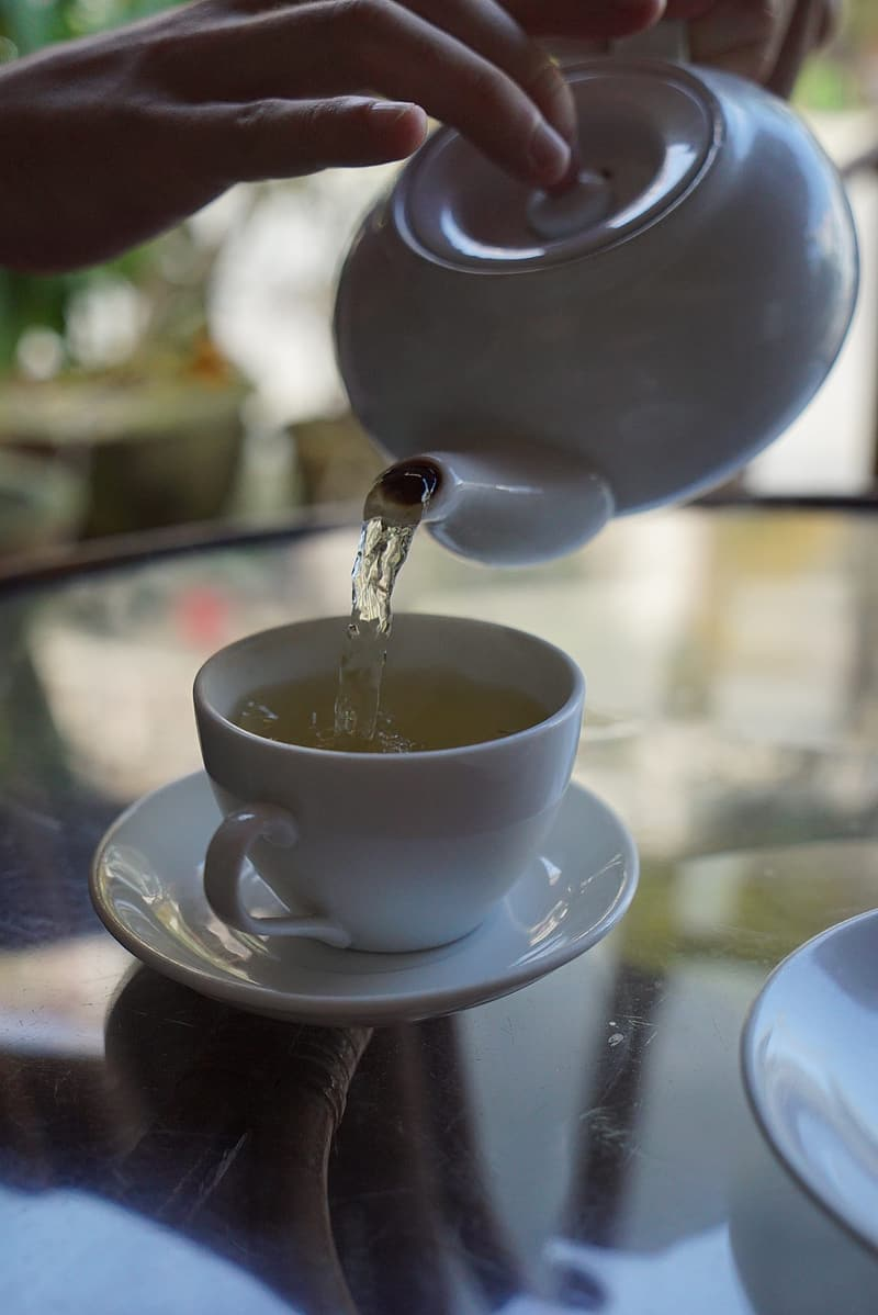 Person pouring beverage from teapot to mug