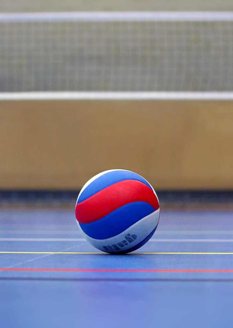 Blue, white, and red volleyball ball near white net on ground