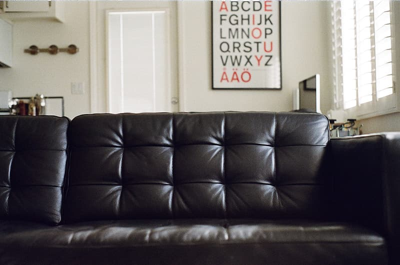 Black leather couch near white wooden door