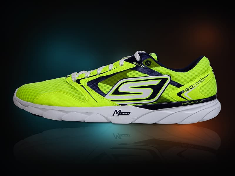 Green and white low-top running shoe