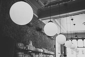 Grayscale photo of pendant lamps near wall