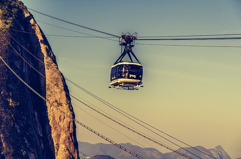 White and black cable car near cliff
