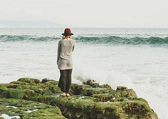 Woman in white long sleeve shirt and black pants standing on rock by the sea during