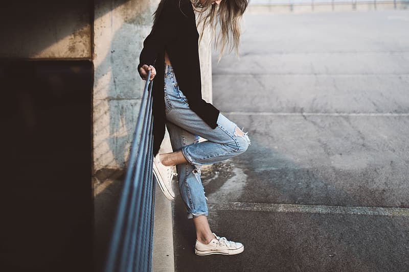 Woman in black long sleeve shirt and blue denim jeans sitting on concrete wall during daytime