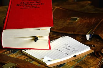 Red and white book on brown wooden table