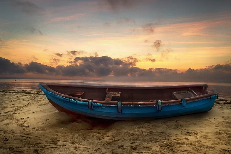 Blue and brown boat on brown sand during sunset