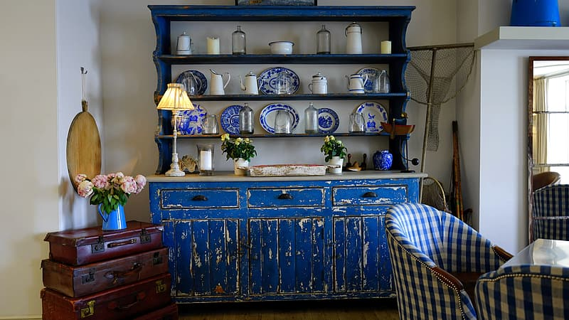 Blue wooden sideboard with rack near chairs