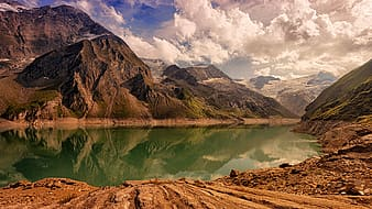 Lake in the middle of mountains under white clouds and blue sky