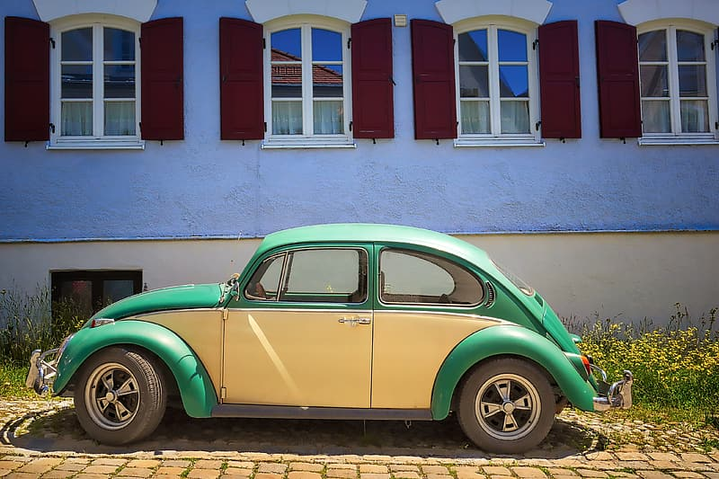 Green volkswagen beetle parked beside white and red concrete building during daytime