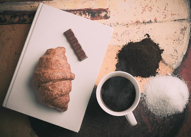 White ceramic coffee cup with coffee near black and white powders near baked bread on white ceramic plate
