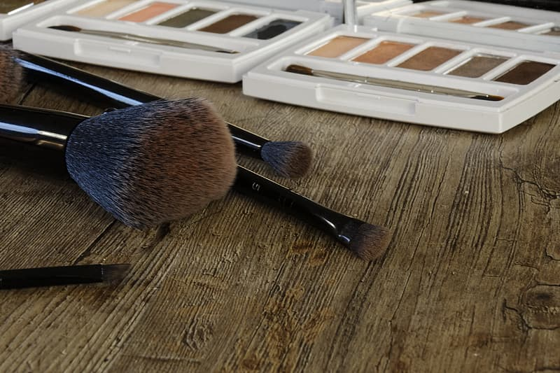 Black makeup brush near white makeup palette