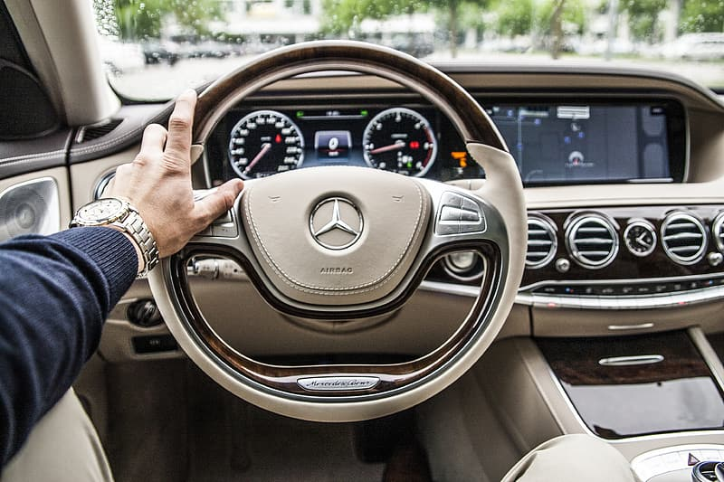 Person holding black mercedes benz steering wheel