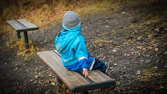 Baby in blue jacket sitting on bench