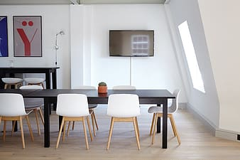 Rectangular black wooden dining table and white chairs