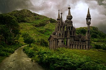 Gray castle on green grass field under cloudy sky