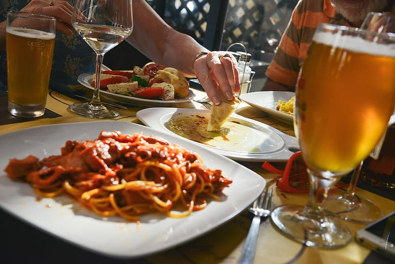 Spaghetti on square white ceramic plate beside stainless steel fork
