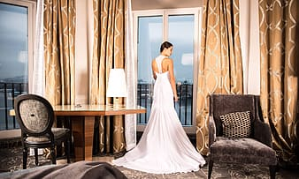 Women's on white wedding gown near door