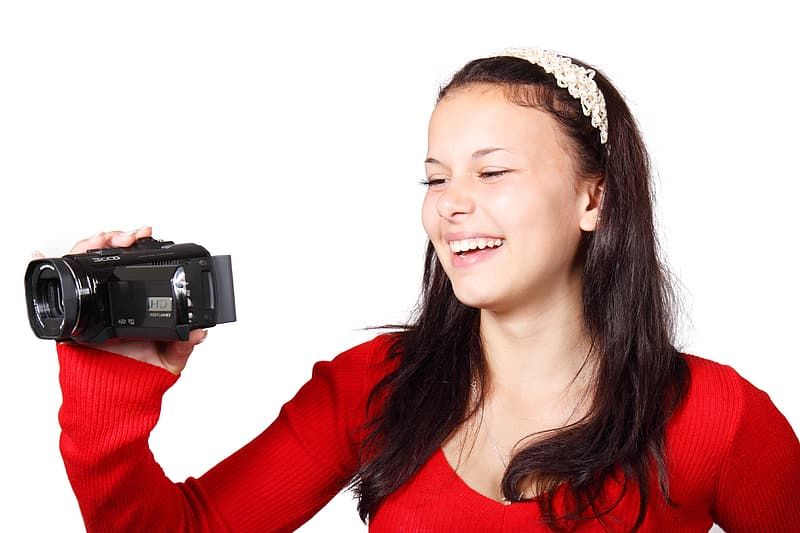 Woman smiling while holding video camera