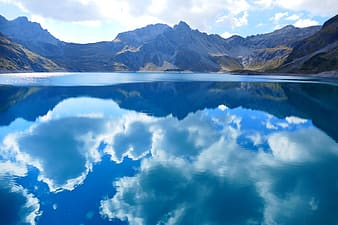 Clear blue water reflecting the sky between mountain ranges during day time